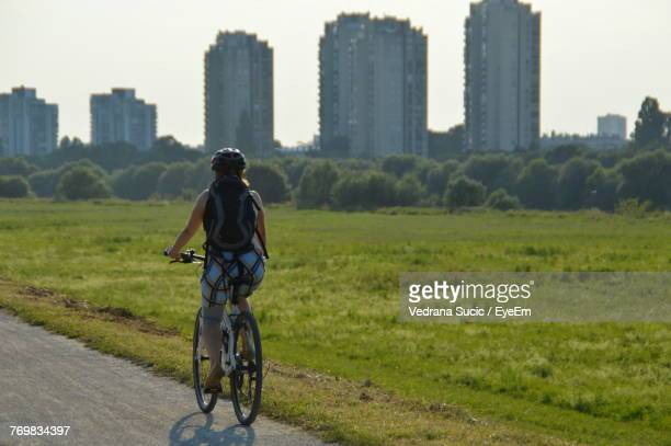 Rear View Of Woman Riding Bicycle In City