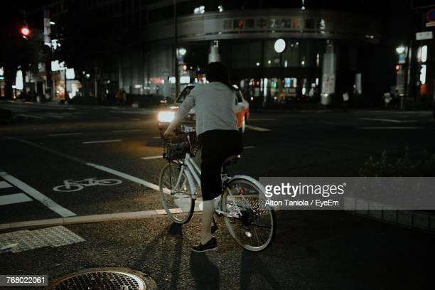 Rear View Of Woman Riding Bicycle On City Street