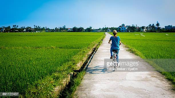 Rear View Of Woman Riding Bicycle On Footpath Amidst Farm