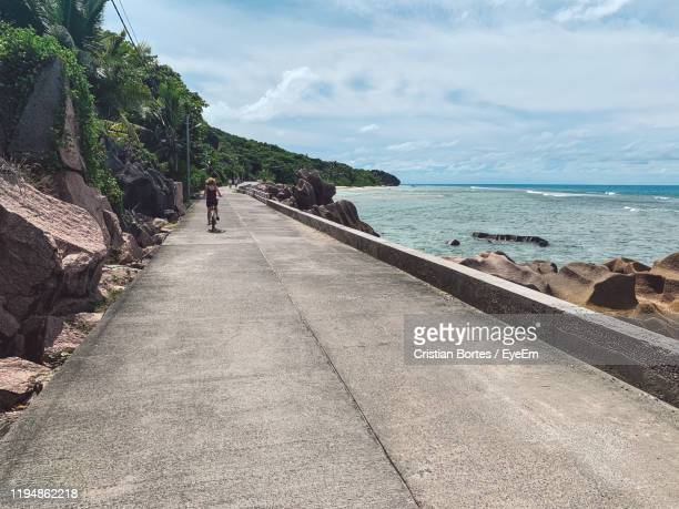 rear view of woman riding bicycle on road by sea - bortes foto e immagini stock