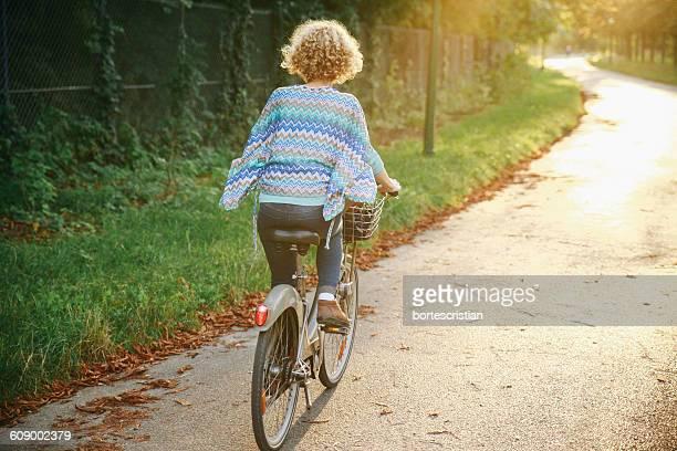 rear view of woman riding bicycle on road - bortes fotografías e imágenes de stock