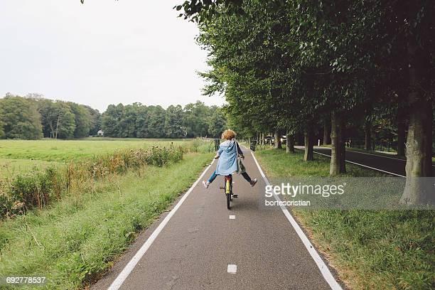 rear view of woman riding bicycle on road - tvåhjulig cykel bildbanksfoton och bilder