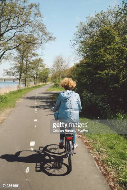 Rear View Of Woman Riding Bicycle On Road