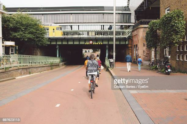 rear view of woman riding bicycle on street against building in city - haarlem stock photos and pictures