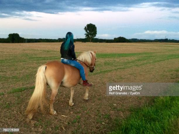 Rear View Of Woman Riding Icelandic Horse On Field