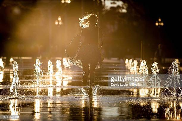 Rear View Of Woman Running By Fountain At Street