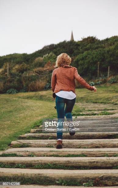 Rear View Of Woman Running On Boardwalk Against Sky