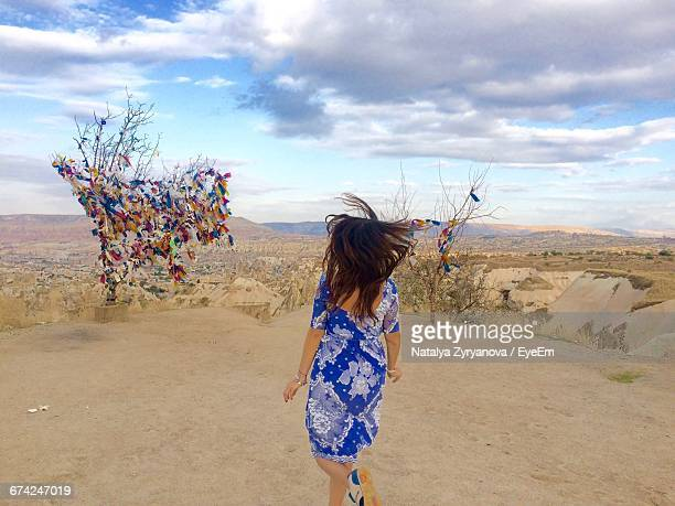Rear View Of Woman Running On Field By Multi Colored Fabrics On Dry Plants Against Sky