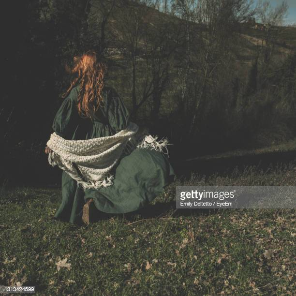 rear view of woman running on field - shawl stock pictures, royalty-free photos & images