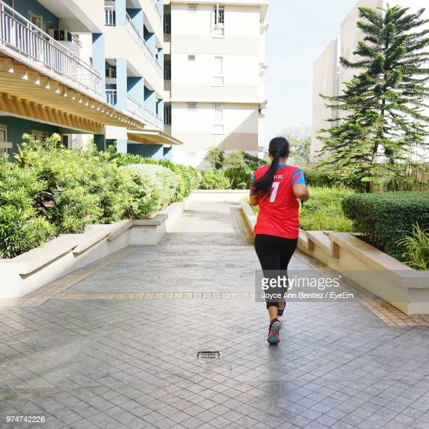 Rear View Of Woman Running On Footpath