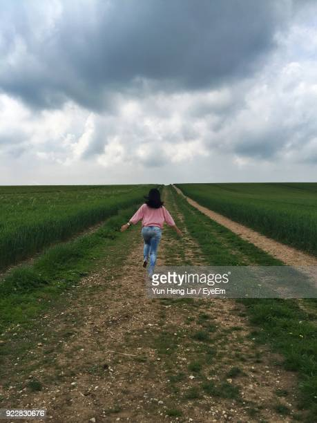 Rear View Of Woman Running On Grassy Field Against Cloudy Sky