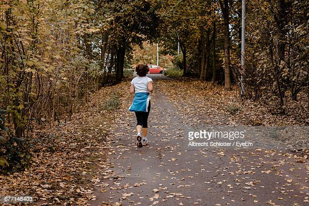 rear view of woman running on leaves covered road - albrecht schlotter stock photos and pictures