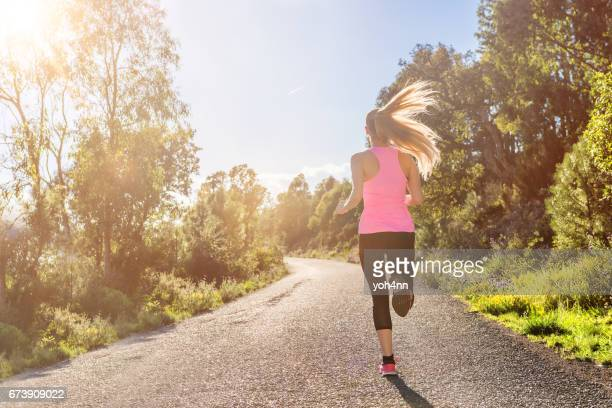 rear view of woman running on road - forward athlete stock pictures, royalty-free photos & images