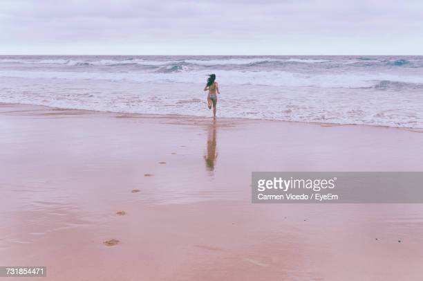 Rear View Of Woman Running On Shore At Beach