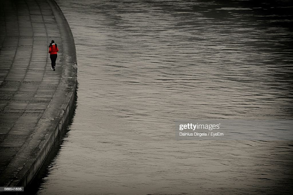 Rear View Of Woman Running On Sidewalk By Lake : Stock Photo