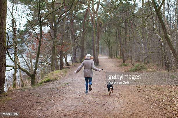 Rear view of woman running with her dog in forest