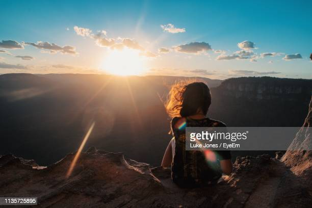 rear view of woman sitting against sky during sunset - katoomba stock pictures, royalty-free photos & images