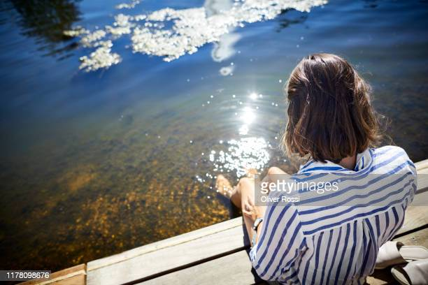 rear view of woman sitting at a pond with feet in water - ruhen stock-fotos und bilder