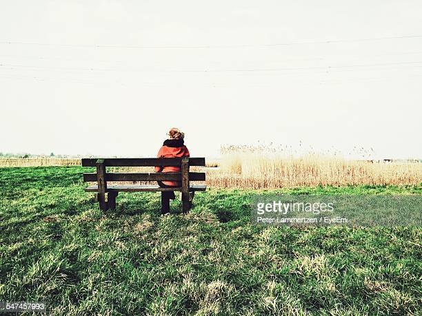 Rear View Of Woman Sitting At Bench On Grassy Field Against Clear Sky