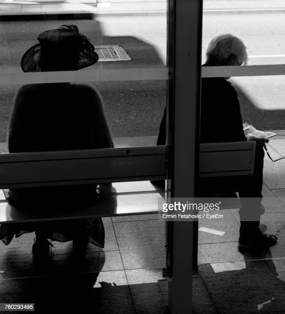 Rear View Of Woman Sitting At Bus Stop
