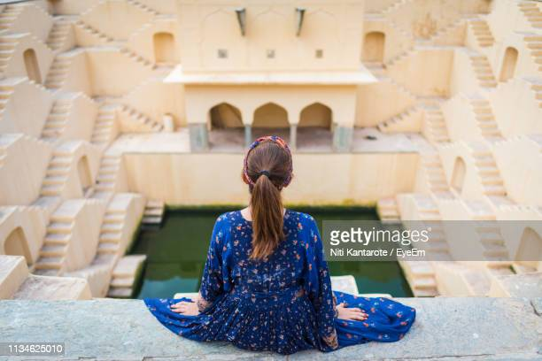 rear view of woman sitting at chand baori - abhaneri stock photos and pictures
