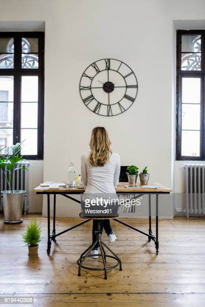 rear view of woman sitting at desk at home under large wall clock - wall clock stock pictures, royalty-free photos & images