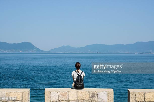 Rear View Of Woman Sitting At Lakeshore Looking At View