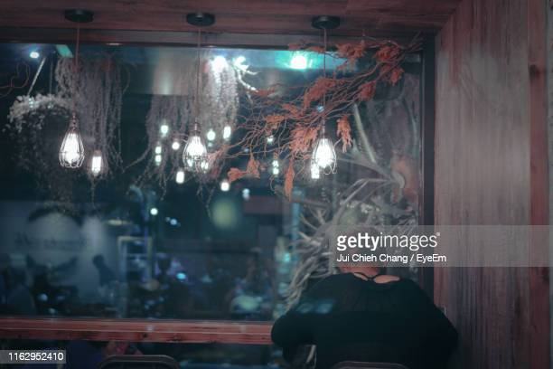 rear view of woman sitting at table in cafe - chang jui chieh imagens e fotografias de stock