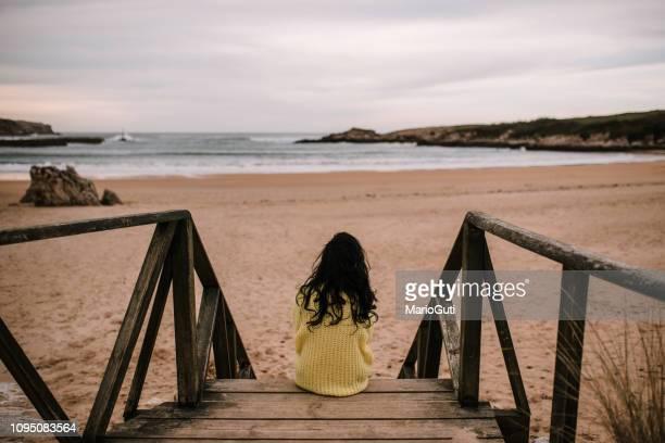 vista posterior de la mujer sentada en una playa - espalda chica morena playa fotografías e imágenes de stock