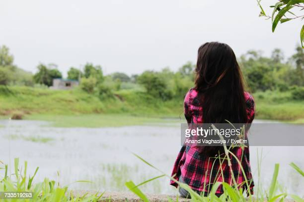 Rear View Of Woman Sitting By Pond