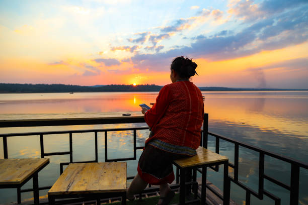 Rear View Of Woman Sitting By Railing Against Sky During Sunset
