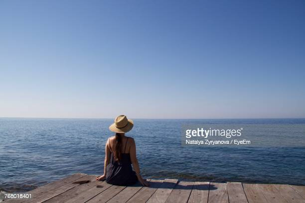 Rear View Of Woman Sitting By Sea Against Clear Sky