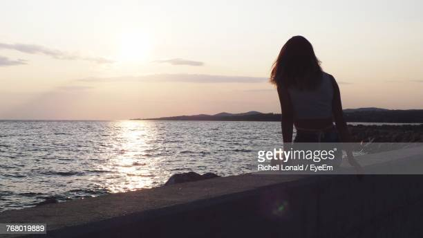 Rear View Of Woman Sitting By Sea Against Sky During Sunset