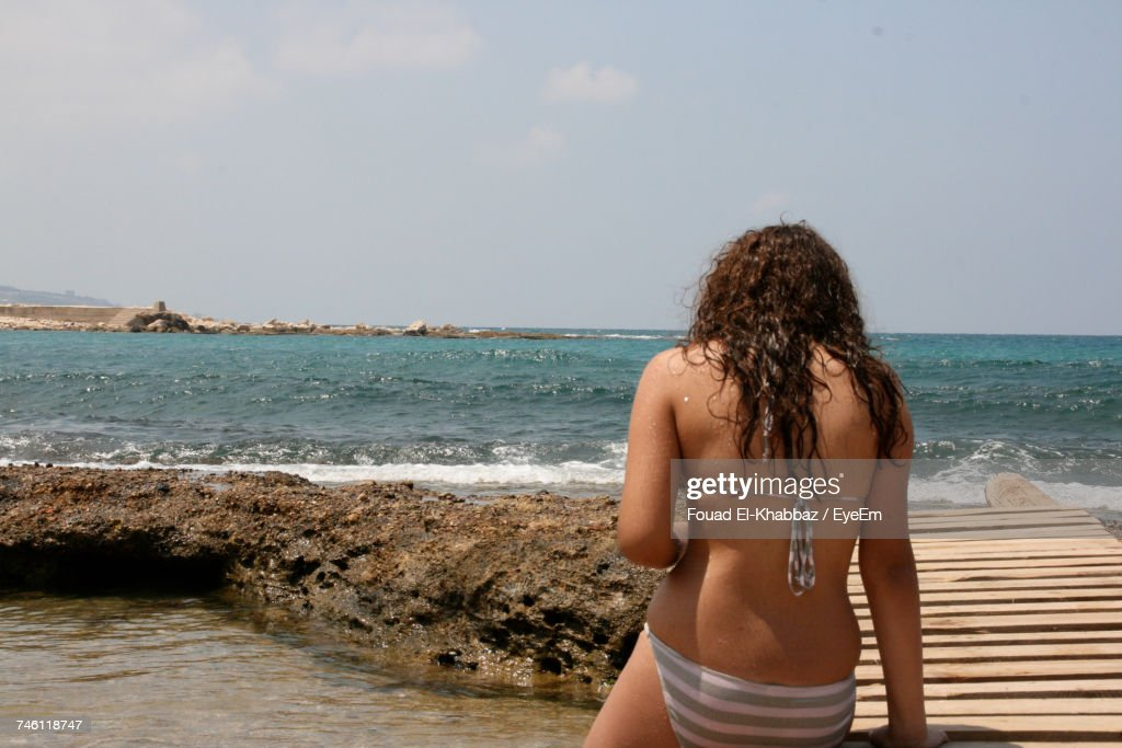 Rear View Of Woman Sitting In Bikini At Beach Against Sky : Stock Photo