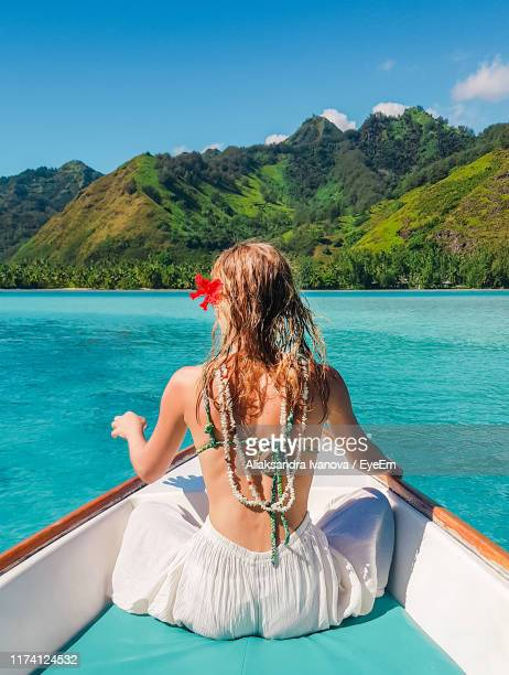 rear view of woman sitting in boat on sea against blue sky - tahiti stock pictures, royalty-free photos & images