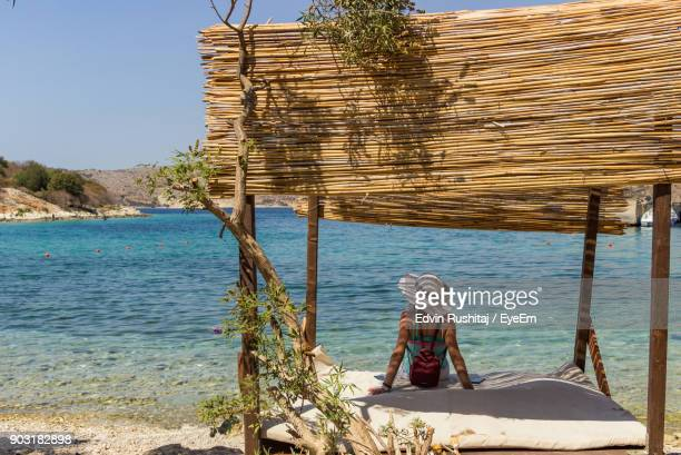 rear view of woman sitting in gazebo at beach - albania stock-fotos und bilder