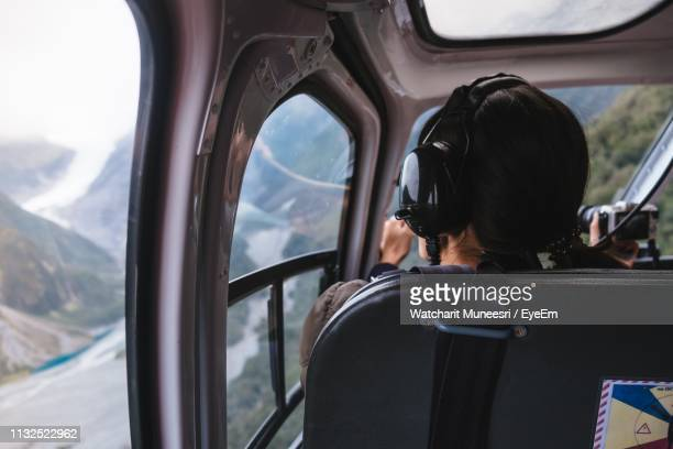 rear view of woman sitting in helicopter cockpit - piloting stock pictures, royalty-free photos & images
