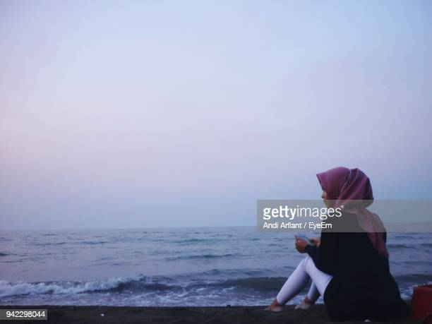 rear view of woman sitting on beach against clear sky - muslim woman beach stock photos and pictures