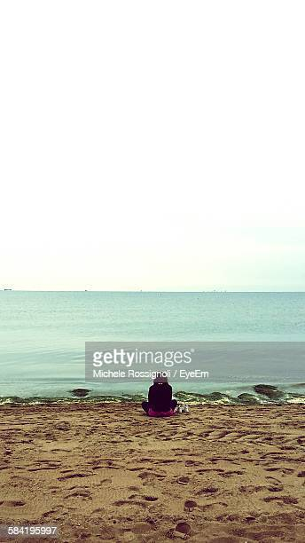 rear view of woman sitting on beach by sea against sky - one young woman only stock pictures, royalty-free photos & images
