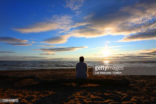 rear view of woman sitting on beach during sunset - vacations stock pictures, royalty-free photos & images