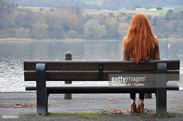 rear view of woman sitting on bench against lake - park bench stock pictures, royalty-free photos & images
