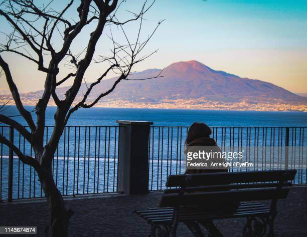 rear view of woman sitting on bench against sea during sunset - one young woman only stock pictures, royalty-free photos & images