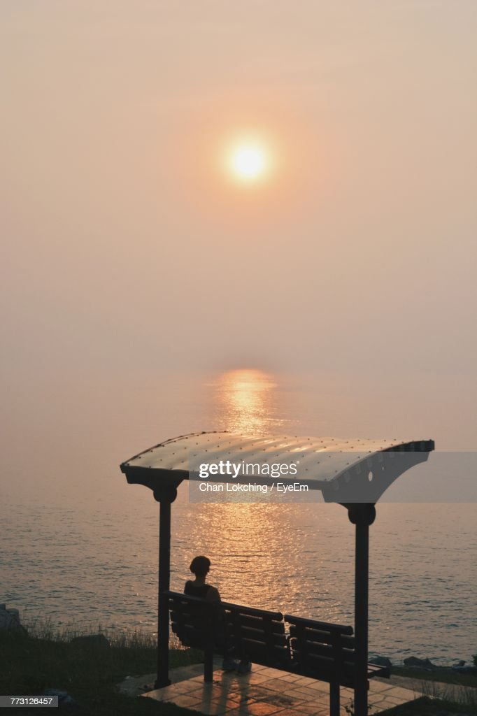 Rear View Of Woman Sitting On Bench Against Sea During Sunset : Photo