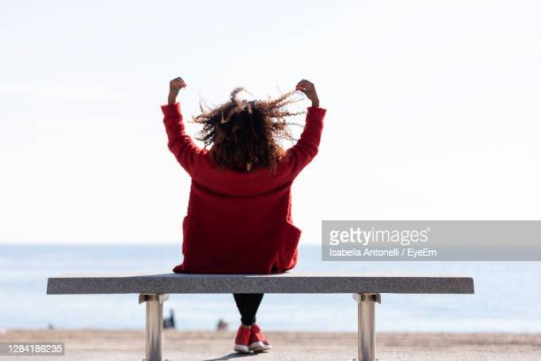 rear view of woman sitting on bench at beach against sky - bench stock pictures, royalty-free photos & images