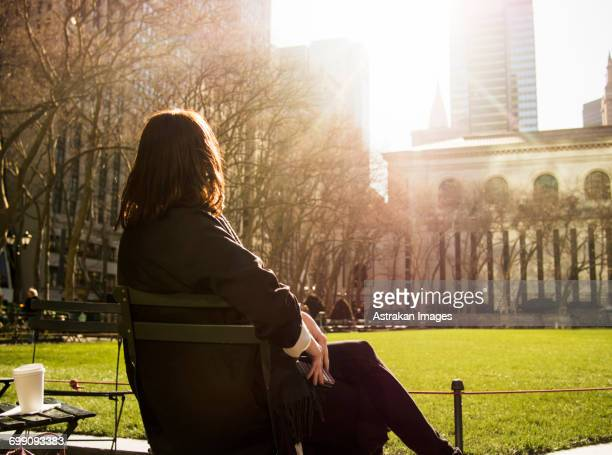 rear view of woman sitting on bench at bryant park during sunny day - ブライアント公園 ストックフォトと画像