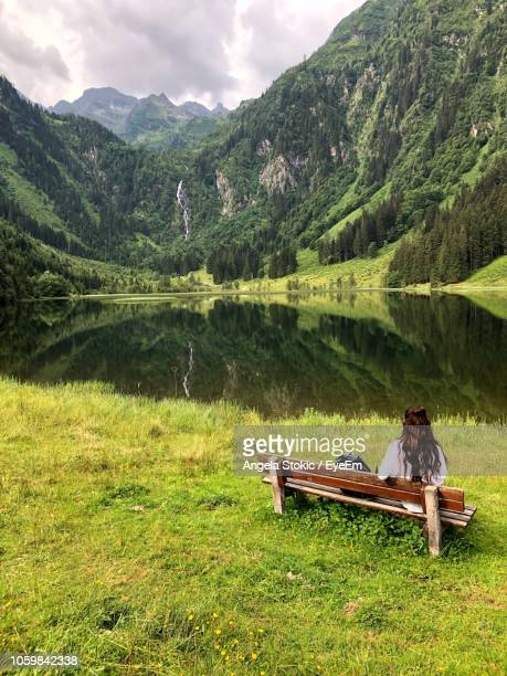 Rear View Of Woman Sitting On Bench By Lake Against Mountains