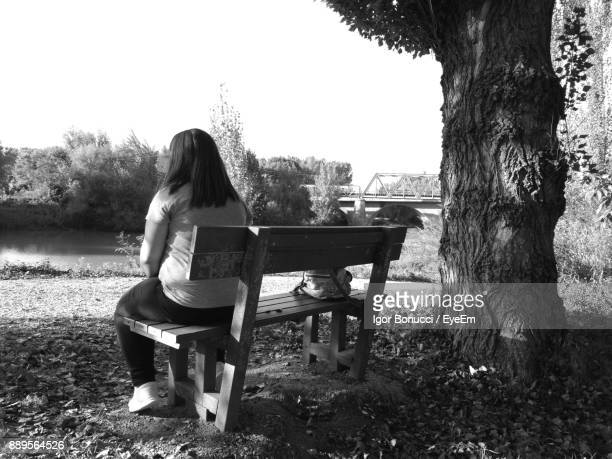 Rear View Of Woman Sitting On Bench By Lake