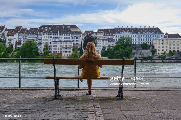 rear view of woman sitting on bench by river in city - basel switzerland stock pictures, royalty-free photos & images