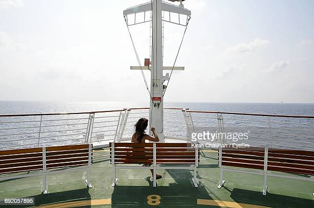 Rear View Of Woman Sitting On Bench In Cruise Ship By Sea Against Sky