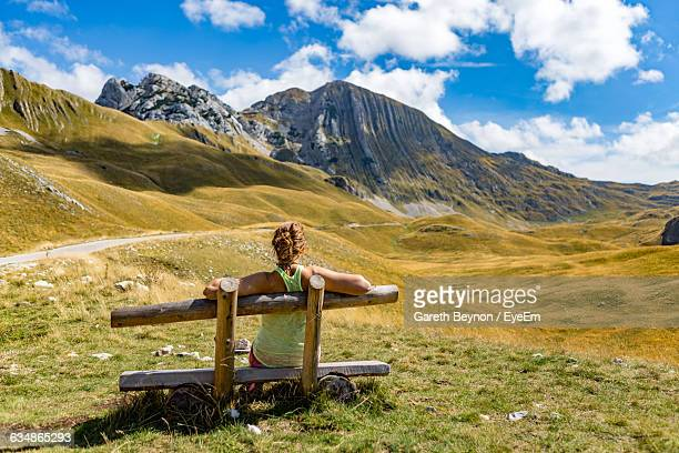 Rear View Of Woman Sitting On Bench In Front Of Mountains